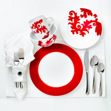 four pieces of red and white dinnerware featuring a damask design set on a white place mat with several pieces of silverware