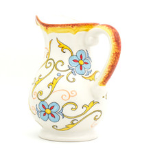 back view of An ornately decorated pitcher with a large lip and a gold and turquoise floral design showing the golden decoration on the handle