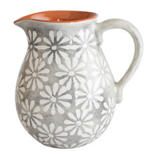 round pitcher with a grey and white floral design and a terra cotta interior and a grey handle