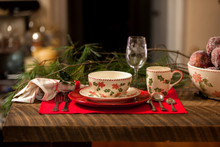 place setting of dinnerware featuring a holly and berry design on a wooden table overlooking a spacious room with evergreen accents