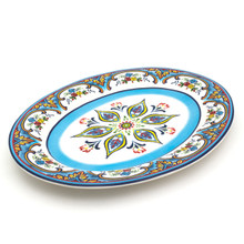 angled view of oval platter featuring a colorful feather floral design and blue brushwork
