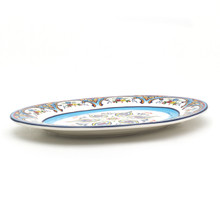 side view of oval platter featuring a colorful feather floral design and blue brushwork
