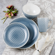 place setting of a grey crackle glaze dinnerware set on a grey background with white napkin