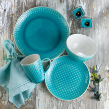 place setting of a turquoise crackle glaze dinnerware set on a grey background with blue napkin
