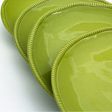 detail view of four green dinner plates showing the beaded detail around the rim and thickness of the plates