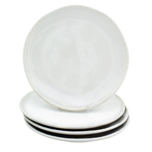 Four white salad plates with beaded detail around the rim. three are stacked and the fourth sits upright on top of the stack