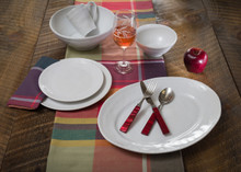 lifestyle view of several pieces of white dinnerware plus oval platter and serving bowl with beaded detailing around the rims. the plates are laid on a warm wooden table with plaid table runner. the photo is propped with a wine glass, silverware, and a single apple.
