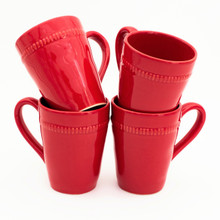 Four red mugs with beaded decoration around the rims displayed in two stacks