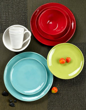assortment of red, white, green, and blue dinnerware laid against a deep background and accented with several pieces of gooseberry
