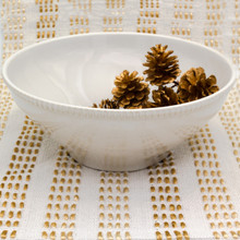 a large white serving bowl with beaded accents around the rim filled with pine cones against a background of gold and white stripes