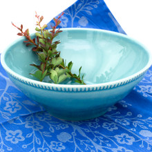 a large blue serving bowl with beaded accents around the rim filled with herbs and placed against a background of blue cloth