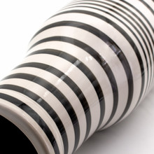 detail shot of a A tall and squarish white and black vase with hand-painted stripe design