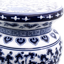 detail view of A traditional chinese garden stool with a blue and white lotus hand-painted design. The stool features a narrow neck and a flat podium platform at the top with a rounded body.