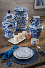 Lifestyle view of A traditional chinese garden stool with a blue and white lotus hand-painted design. The stool features a narrow neck and a flat podium platform at the top with a rounded body. Featuring the matching Ginger jar and handled vase, plus dinnerware accents and some candles on  a soft wood background.