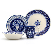 a place setting of blue hand-painted floral dinnerware: a shallow soup bowl, a mug, a salad plate, and a dinner plate