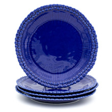 stack of three blue dinner plates with two rings of beads around the rim, a fourth plate standing on the stack