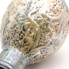 Detail view of A shiny somewhat metallic vase with a coppery top, brown body, and deep blueish green bottom. The vase features engraved and embossed abstract details that resemble seaweed and a ship wheel and is marked all over with small indents like scales.