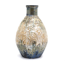 A shiny somewhat metallic vase with a coppery top, brown body, and deep blueish green bottom. The vase features engraved and embossed abstract details that resemble seaweed and a ship wheel and is marked all over with small indents like scales.