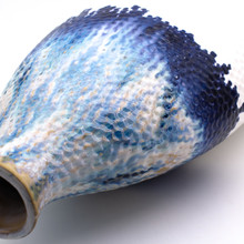 Detail view of a flattened shoulder vase. The vase features shades of blue glaze dripping from the top that transition to a flat white. The vase is marked all over with small indents like sand that has been brushed by the tide.
