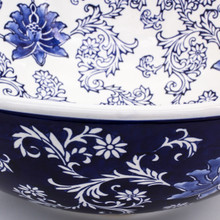 detail shot of a large wide bowl with dark blue exterior and white interior decorated with a hand-painted lotus design showing both the exterior and interior brushwork