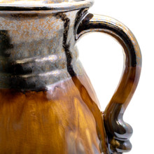 Detail of metallic decorative pitcher with coppery lip, stripe of brown dripping crackle glaze, reflective metallic bottom and a swirled decoration on the handle showing the handle and texture of the brown glaze