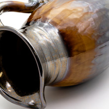 side shot of metallic decorative pitcher with coppery lip, stripe of brown dripping crackle glaze, reflective metallic bottom and a swirled decoration on the handle showing the shape of the lip and neck