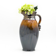 lifestyle shot of metallic decorative pitcher with coppery lip, stripe of brown dripping crackle glaze, reflective metallic bottom and a swirled decoration on the handle featuring a small bouquet of yellow artificial flowers in the mouth