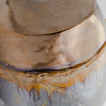detail of large metallic garden stool with engraved leaf designs, roped carving around the top and bottom, drum shape and coppery and reflective metallic glazes