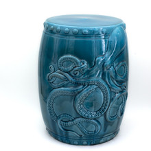 drum shaped turquoise stool with carved kraken or octopus figure across the front with several small bumps along the top