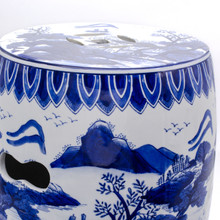 top view of drum shaped blue and white hand-painted stool featuring a traditional chinese landscape painting and two cut-out handles showing three additional cutouts and a continuation of the painting on the top of the stool
