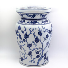 angled view of white garden stool featuring a blue hand-painted cherry blossom design. the stool has a narrow neck and wide flat podium top with a curved body