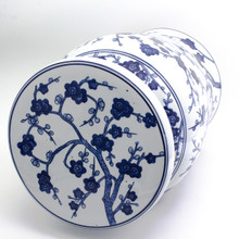 side view of white garden stool featuring a hand-painted cherry blossom design. the stool has a narrow neck and wide flat podium top with a curved body