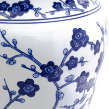 detail shot of white garden stool featuring a blue hand-painted cherry blossom design showing the brushwork of the blue painted design