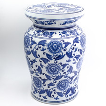 angled view of white garden stool featuring a blue hand-painted begonia design. the stool has a narrow neck and wide flat podium top with a curved body