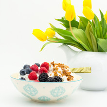 a white bowl with turquoise patterns filled with yogurt and berries. in the background a white teapot contains a bouquet of yellow tulips