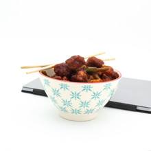a single white bowl with turquoise patterns filled with chinese takeout with a laptop in the background