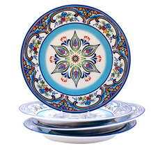 stack of three dinner plates featuring a blue star and floral design with a fourth plate upright on the stack