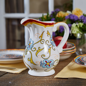 An ornately decorated pitcher with a large lip and a gold and turquoise floral design sits on a dark wooden table and several pieces of dinnerware cut out of the frame