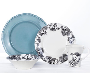 a 16 piece dinnerware set featuring blue dinner plates and grey silhouette floral designs on the bowl, mug and salad plate
