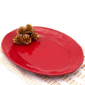 red oval platter with beaded accents around the rim with several pine cones resting on it and a white and gold place mat underneath