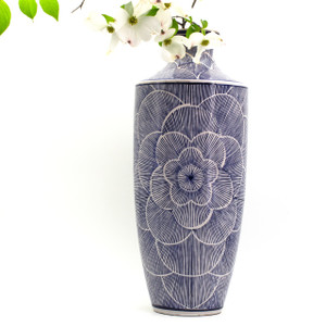 Lifestyle shot of Tall vase with hand-painted line art design showing a large flower in bloom featuring a dogwood branch in the vase