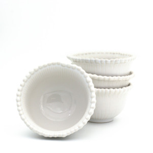 stack of three white bowls with beaded rims with a forth bowl upended to show the inside