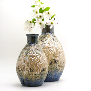 Lifestyle view of A shiny somewhat metallic vase with a coppery top, brown body, and deep blueish green bottom. The vase features engraved and embossed abstract details that resemble seaweed and a ship wheel and is marked all over with small indents like scales. The photo features the larger version of the vase in the background. the larger vase has a branch of dogwood in it.