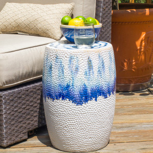 A drum-shaped garden stool with shades of blue glaze dripping from the top that transition to a flat white. The stool is marked all over with small indents like sand that has been brushed by the tide.
