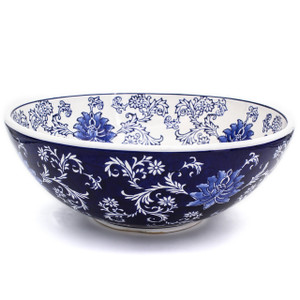 a large wide bowl with dark blue exterior and white interior decorated with a hand-painted lotus design.