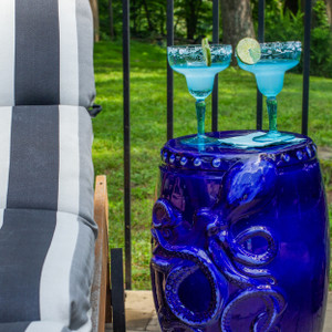 drum shaped cobalt stool with carved kraken or octopus figure across the front with several small bumps along the top with margaritas and a lime on top