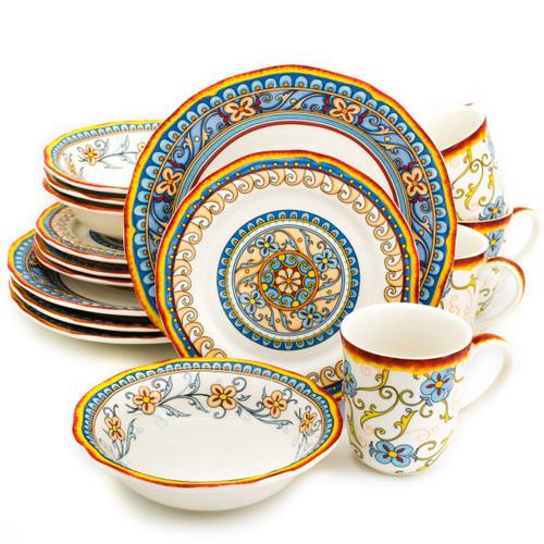 An ornately decorated 16 piece dinnerware set with scalloped edges and a gold and turquoise floral design