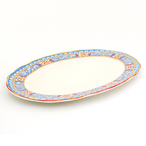 angled view of an ornately decorated oval platter with a scalloped lip and a gold and turquoise floral design