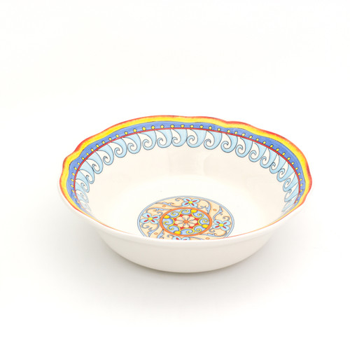 angled view of an ornately decorated serving bowl with a scalloped lip and a gold and turquoise floral design