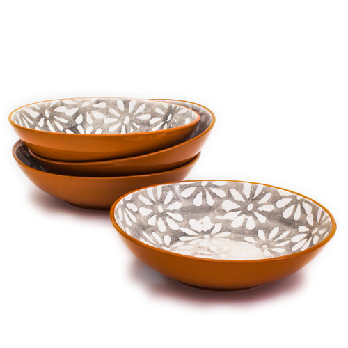 stack of three shallow terra cotta bowls with grey interiors decorated with white flowers and another bowl in front